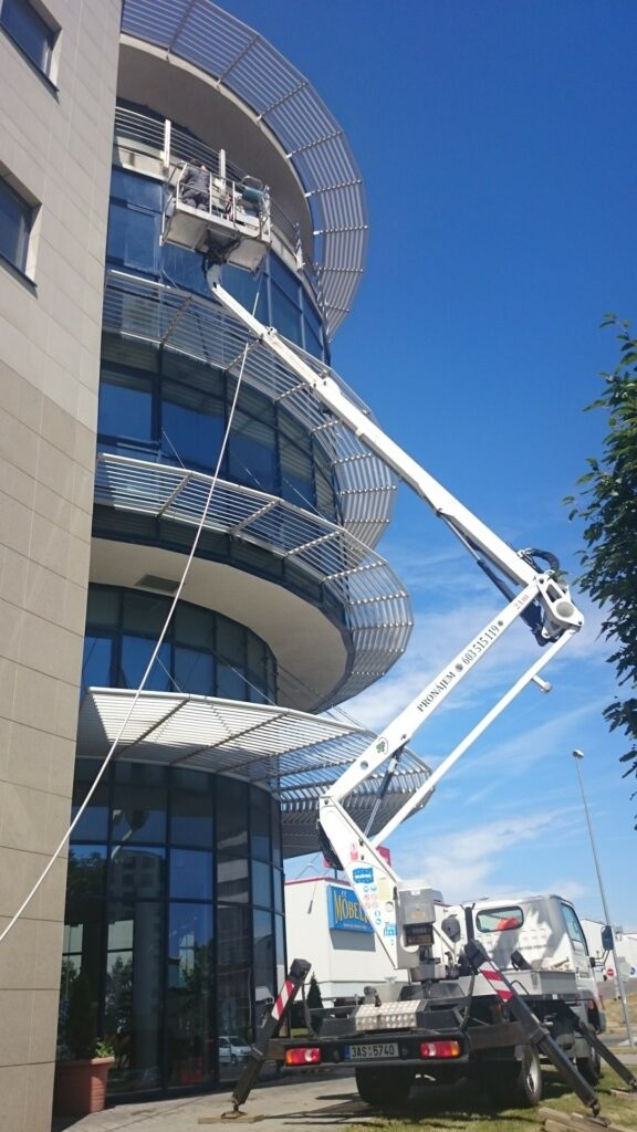Mytí skleněných částí budovy.